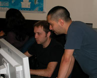 CIESIN Information Technology division members Brian Falk (left) and Andres Gonzalez looking at the course information on the computer monitor during the training.