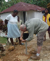 A rain gauge is installed by a researcher and local Haitians.