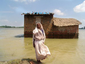 Photo of woman in front of her mud home which is surrounded by floodwaters.