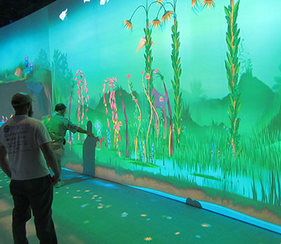 Visitor gesturing at Connected Worlds exhibit