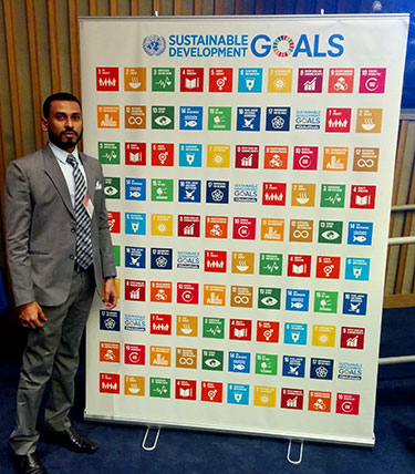 Fulbright-Nehru Fellow Saleem Khan stands by a poster illustrating the Sustainable Development Goals.